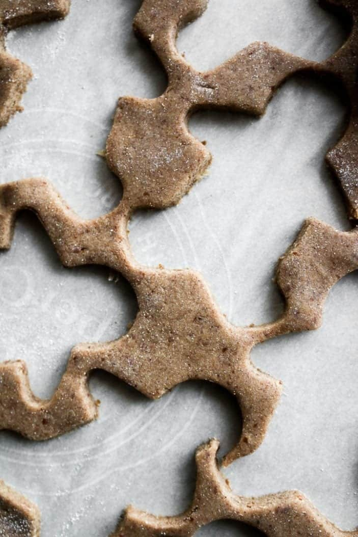 Chai-Spiced Cut-Out Cookies dough with gingerbread men removed from the dough.