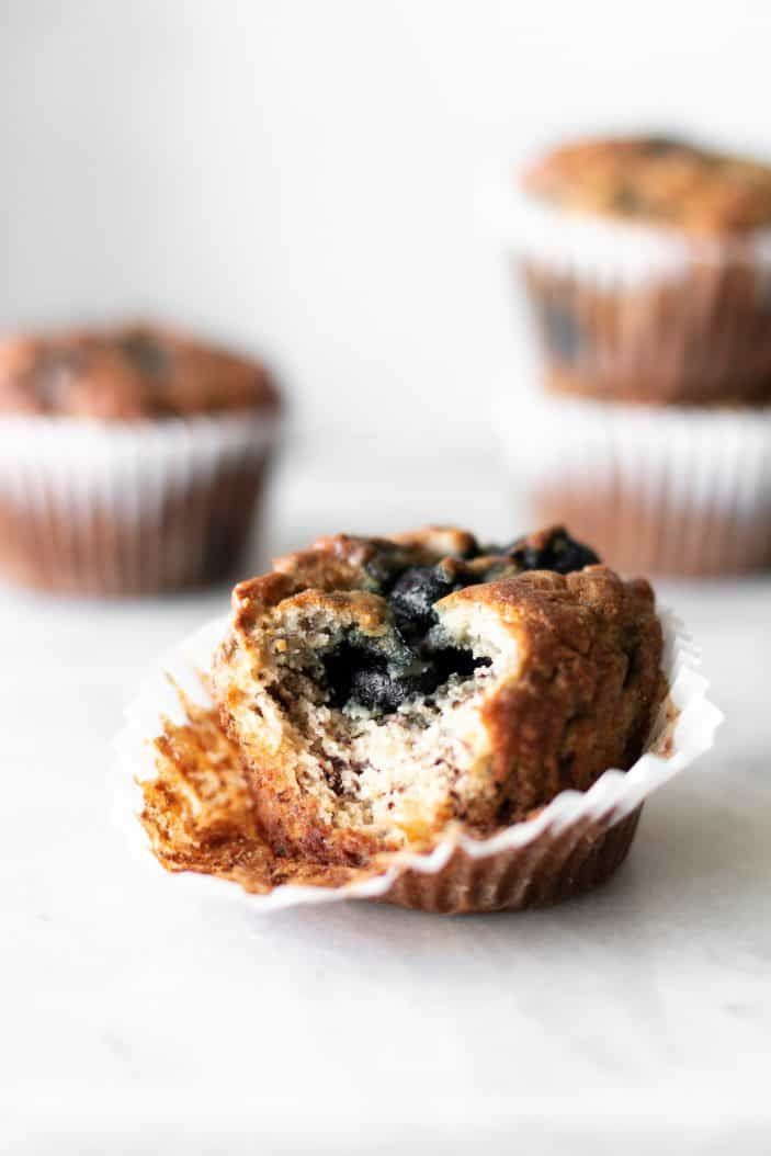 blueberry banana almond flour muffins with bite taken from it