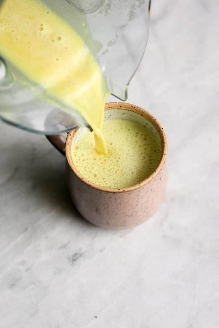 Warm Turmeric Ginger Milk poured in cup - cozy blender drinks