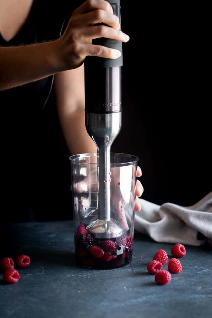berries being blended with hand blender