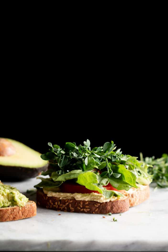 open hummus avocado sandwich from the side