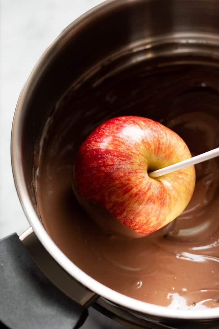 apple being dipped in chocolate