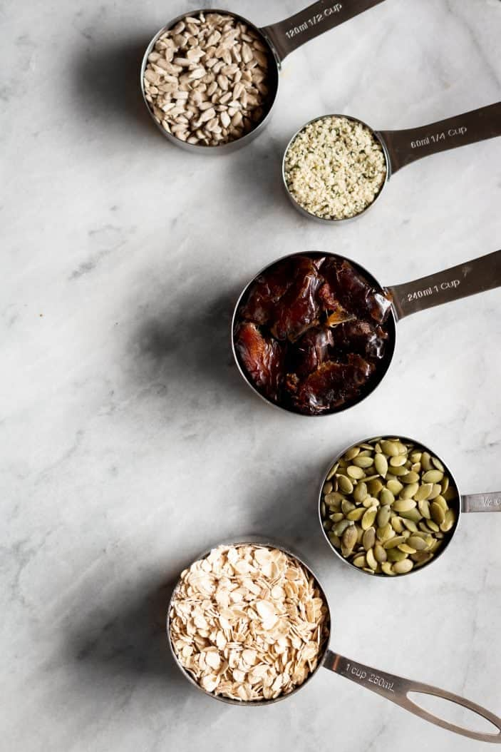 seeds, dates and oats in measuring cups