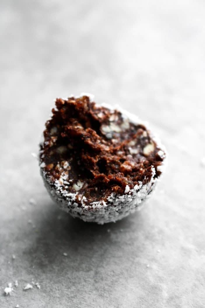 One Dreamy Coconut Macaroon Truffle with a bite taken from it.