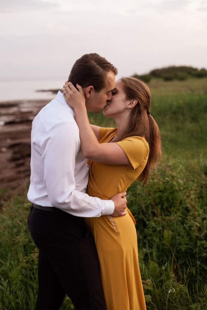 couple kissing in tall grass
