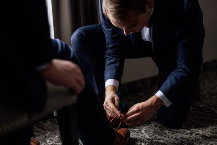 groom lacing brother's shoes