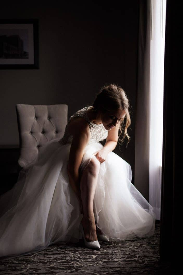 bride in dress, putting on shoes