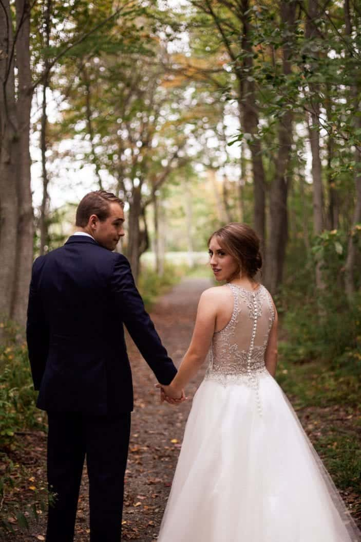 bride and groom walking hand in hand in the forest