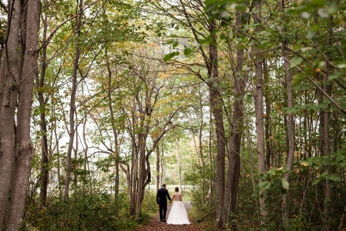 Our rustic chic and cozy fall wedding - bride and groom walking in forest