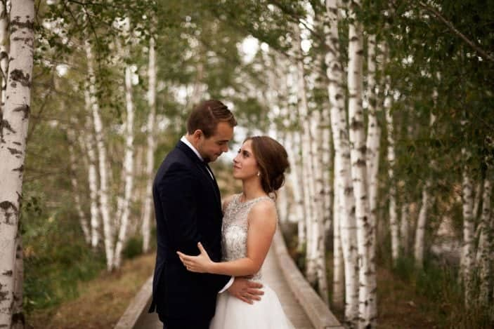 bride and groom looking at each other in forest - cozy fall wedding
