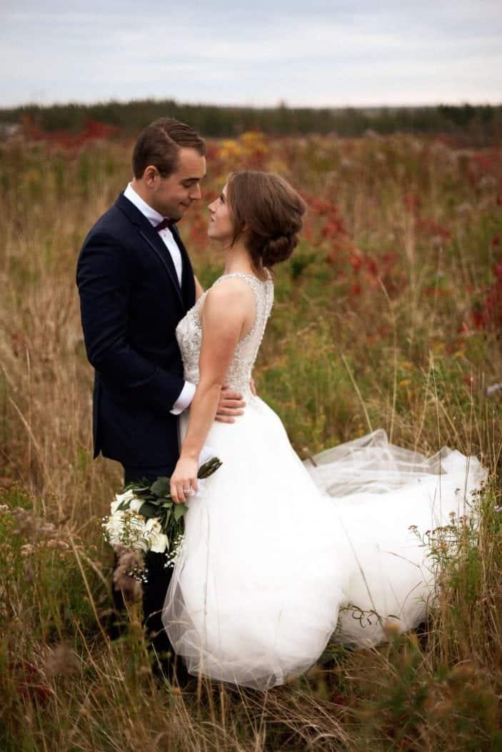 bride and groom in a field - wedding photos
