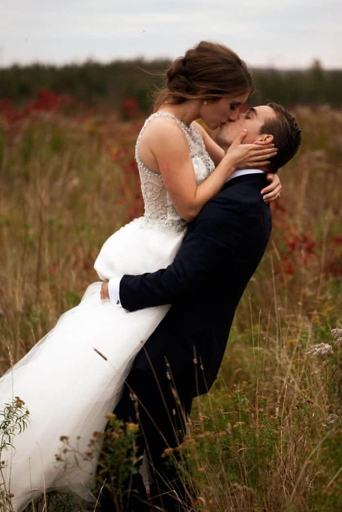 groom holding bride, kissing - wedding photos