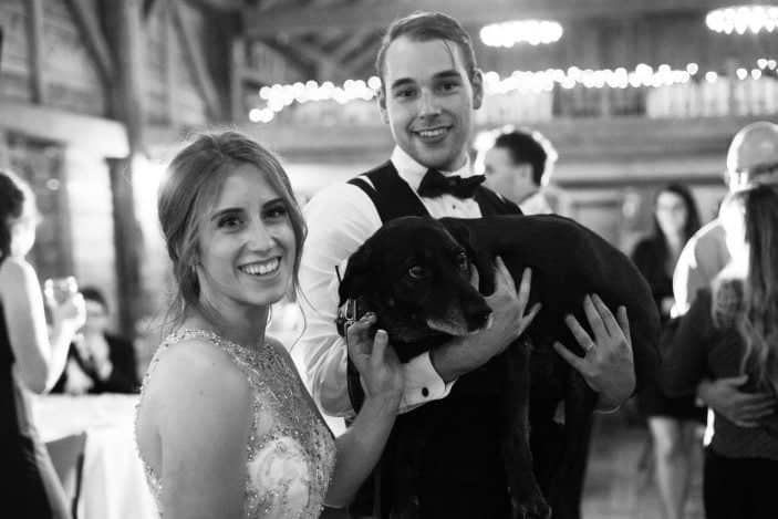 bride and groom holding dog