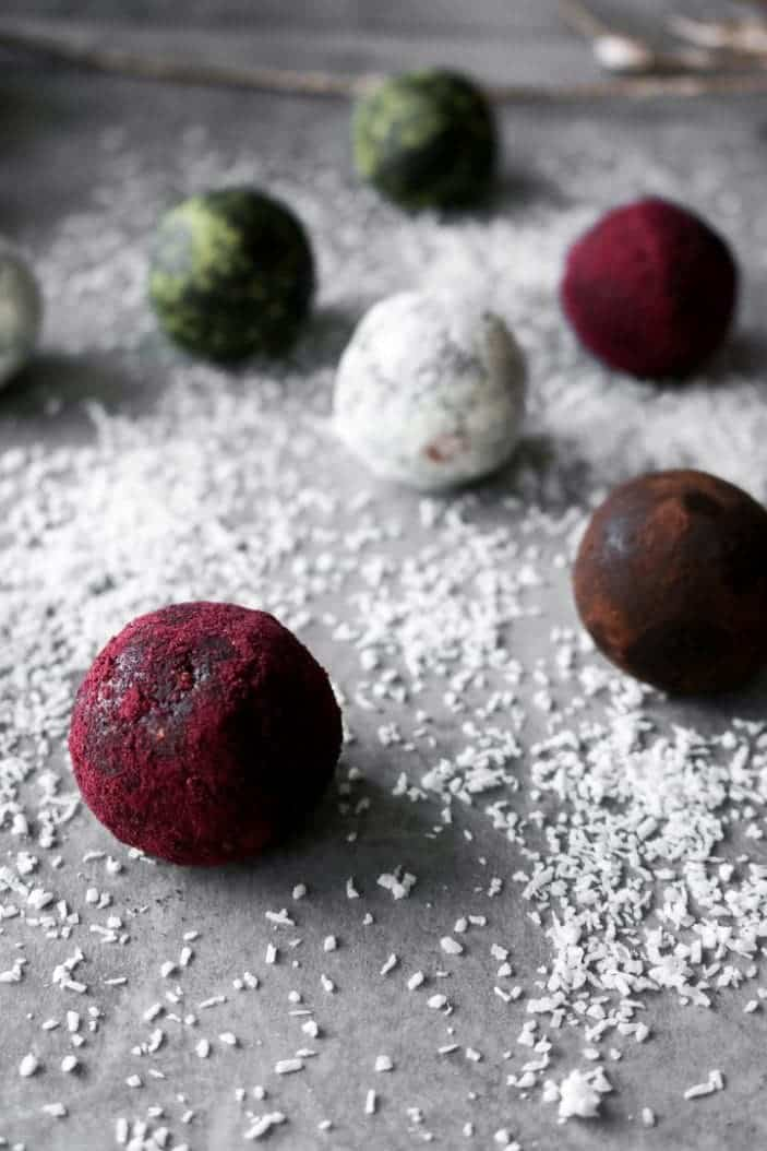 Seven Easy Holiday Truffles seen from the side in different colours ranging from red, brown, white and green.