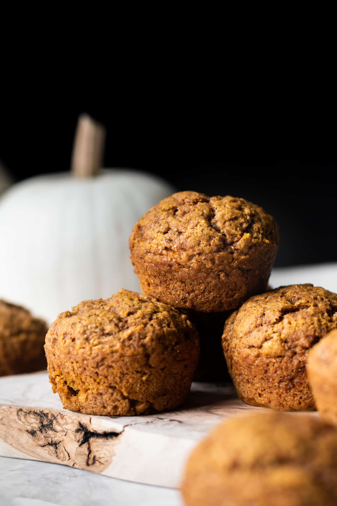 stacked vegan pumpkin muffins from the side