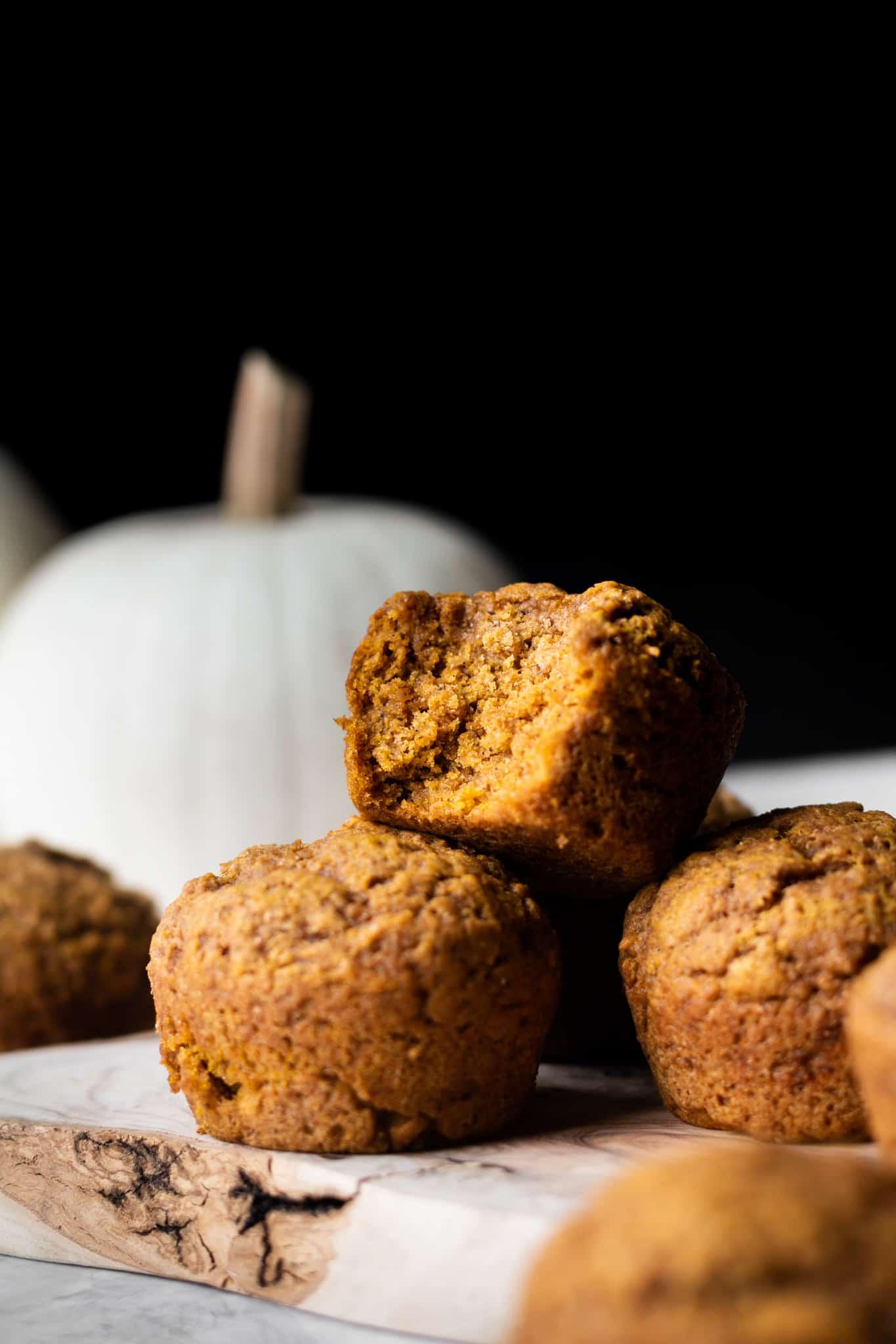 stacked vegan pumpkin muffins with bite taken